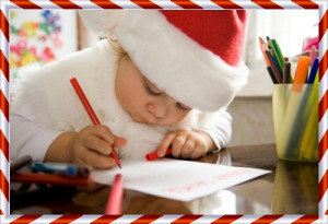 The small child writes the letter to Santa