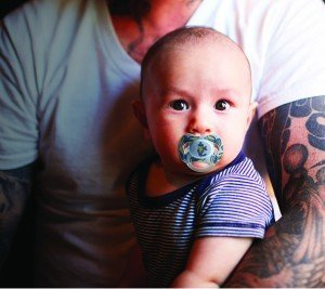 Tattooed father holding his son